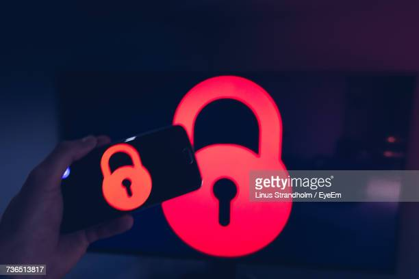 Cropped Hand Of Man Holding Mobile Phone With Lock Icon Against Monitor At Home