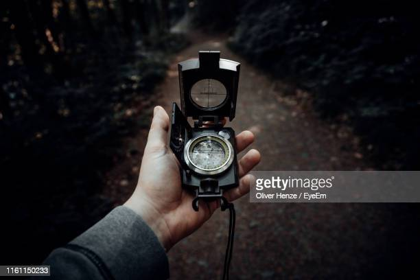 cropped hand of man holding navigational compass - compass stock pictures, royalty-free photos & images