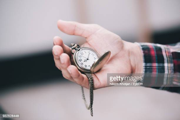 Cropped Hand Of Man Holding Pocket Watch Outdoors