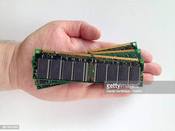 Cropped Hand Of Man Holding Random Access Memories Against White Background