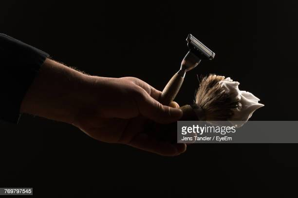 cropped hand of man holding razor and shaving brush against black background - shaving cream stock photos and pictures