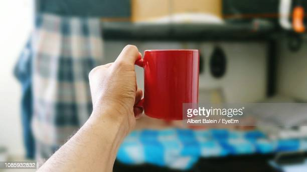 cropped hand of man holding red mug at home - mug stock pictures, royalty-free photos & images
