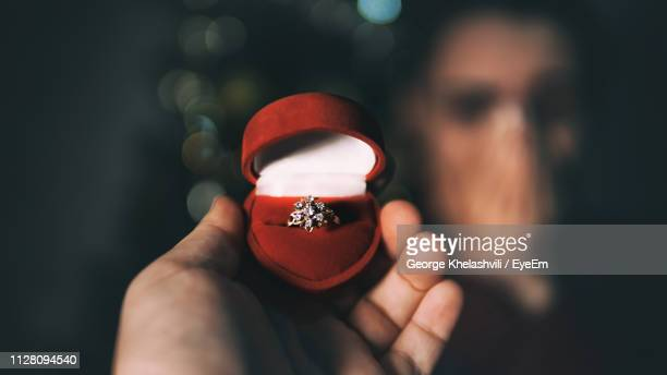 cropped hand of man holding ring in box against surprised woman - 宝石箱 ストックフォトと画像