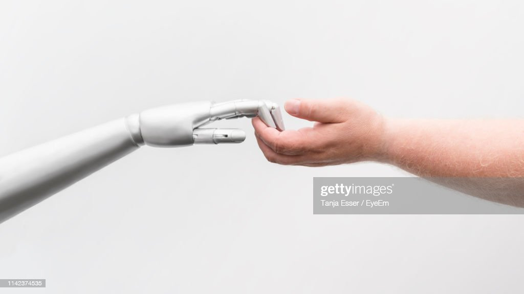 Cropped Hand Of Man Holding Robot Against White Background : Stock Photo