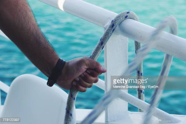 Cropped Hand Of Man Holding Rope At Sea