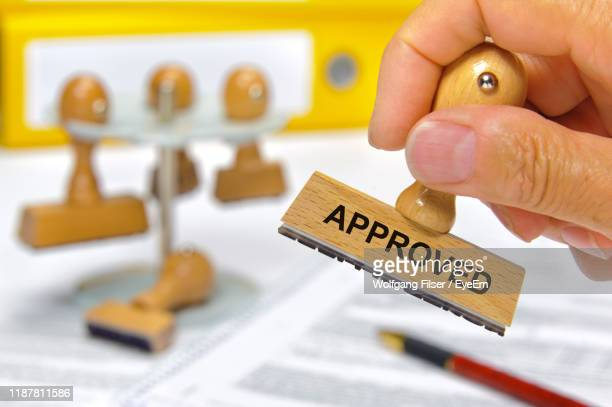 cropped hand of man holding rubber stamp with approved text at desk - permission concept stock pictures, royalty-free photos & images