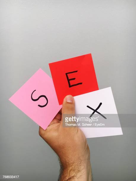 cropped hand of man holding sex text on adhesive tape against wall - x photos stock photos and pictures