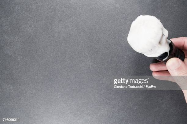 cropped hand of man holding shaving brush with cream by gray wall - shaving brush stock photos and pictures