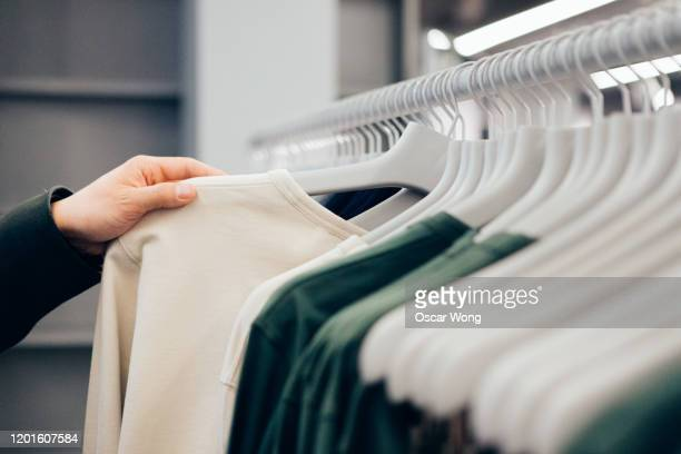 cropped hand of man holding shirt in shop - menswear stock pictures, royalty-free photos & images