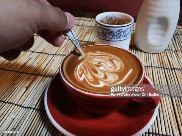 Cropped Hand Of Man Holding Spoon In Coffee At Table