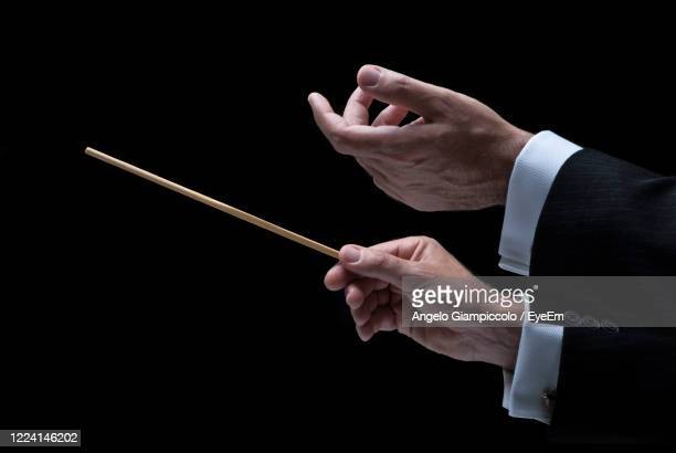 cropped hand of man holding stick against black background - 指揮者 ストックフォトと画像