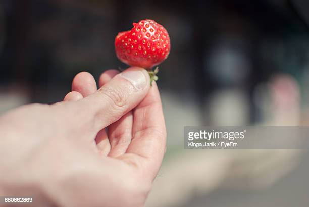 Cropped Hand Of Man Holding Strawberry