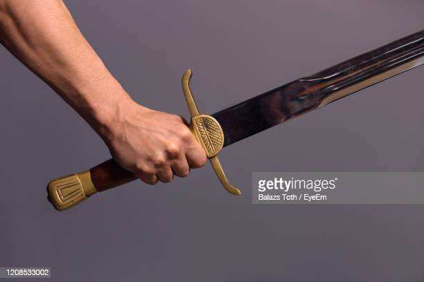 cropped hand of man holding sword against gray background - sword stock pictures, royalty-free photos & images