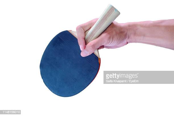 cropped hand of man holding table tennis racket against white background - table tennis racket stock pictures, royalty-free photos & images
