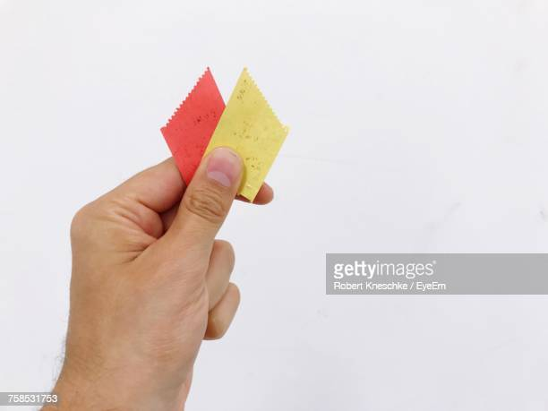 Cropped Hand Of Man Holding Tickets Against White Background