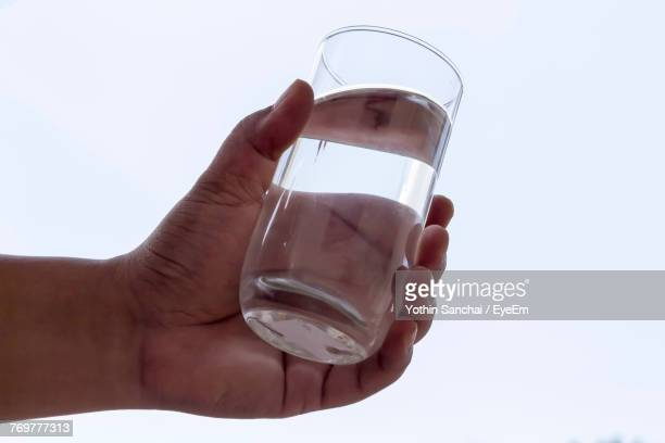 Cropped Hand Of Man Holding Water In Glass Against White Background
