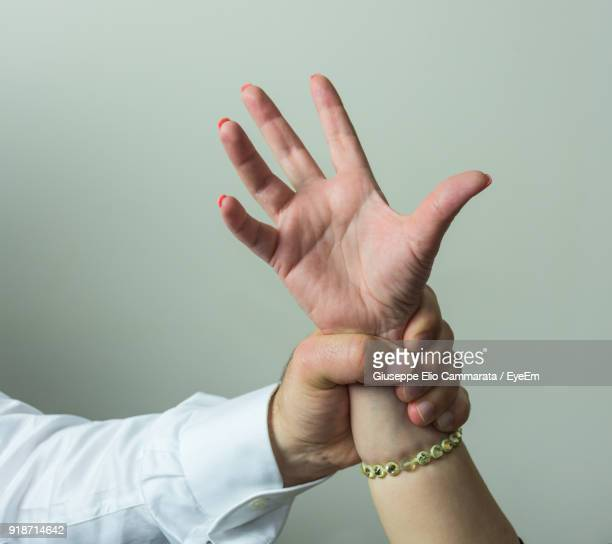 cropped hand of man holding woman against gray background - domestic violence stock pictures, royalty-free photos & images