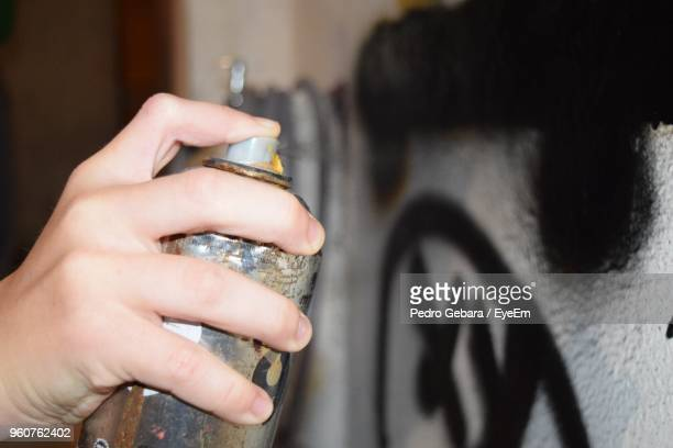 Cropped Hand Of Man Making Graffiti With Spray Paint On Wall