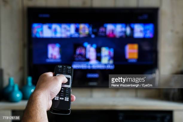 cropped hand of man operating remote at home - televisor - fotografias e filmes do acervo