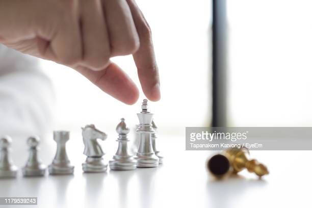 cropped hand of man picking chess piece on table - menschlicher finger stock-fotos und bilder