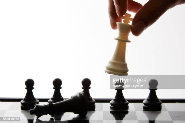 Cropped Hand Of Man Playing Chess Against White Background