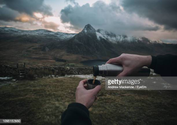 cropped hand of man pouring coffee from insulated drink container against mountains during sunset - flask stock pictures, royalty-free photos & images
