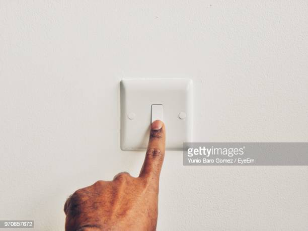 Cropped Hand Of Man Pressing Switch Board Against Wall