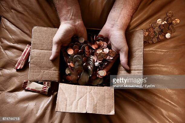 cropped hand of man putting us coins in cardboard box - penny for the guy stock photos and pictures