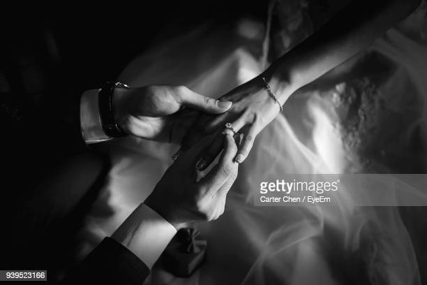 cropped hand of man putting wedding ring to woman - marriage stock pictures, royalty-free photos & images