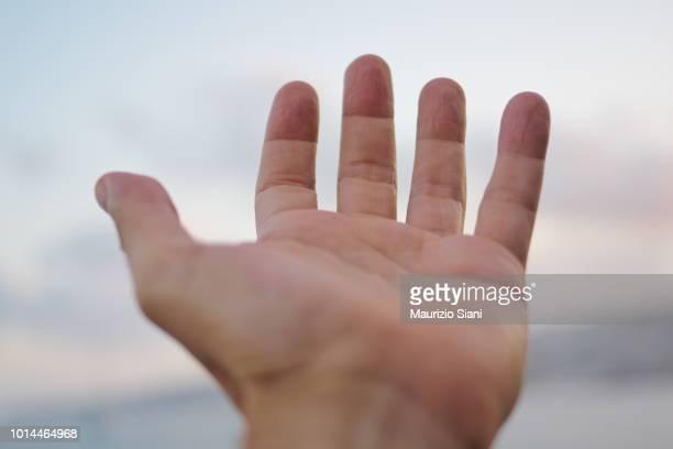 cropped hand of man reaching outdoors - dito umano foto e immagini stock