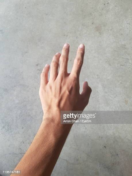 cropped hand of man reaching towards wall - reaching stock pictures, royalty-free photos & images