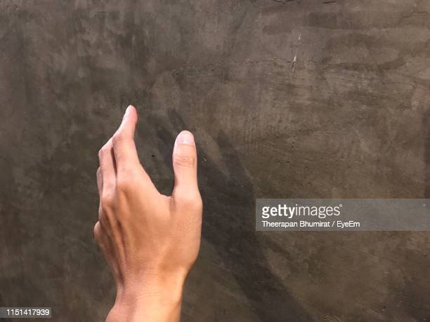 cropped hand of man reaching towards wall - perspective du photographe photos et images de collection