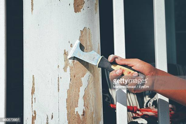 cropped hand of man scraping paint on wall at home - scraping stock photos and pictures