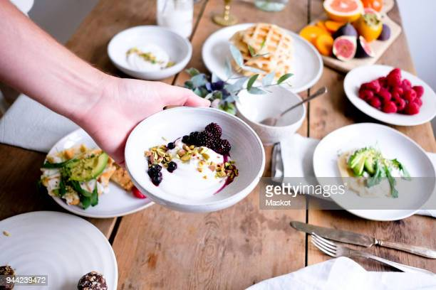 cropped hand of man showing dessert in bowl at table - mid adult men imagens e fotografias de stock