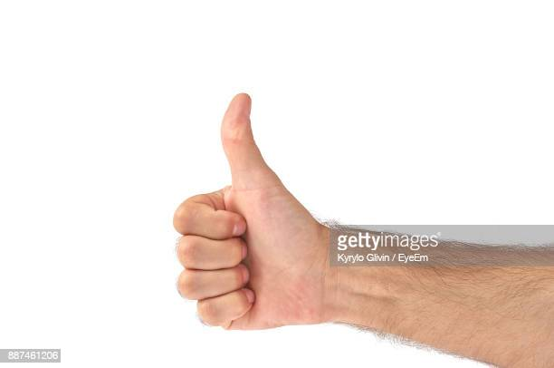 Cropped Hand Of Man Showing Thumbs Up Against White Background