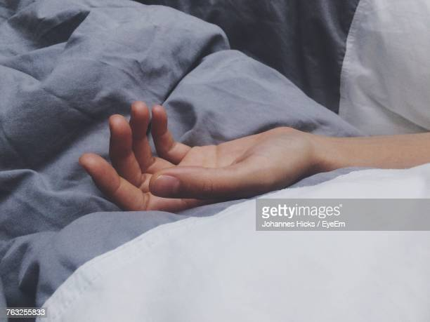 Cropped Hand Of Man Sleeping On Bed