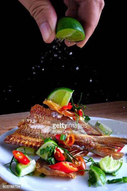 Cropped Hand Of Man Squeezing Lemon Juice On Seafood In Plate Against Black Background