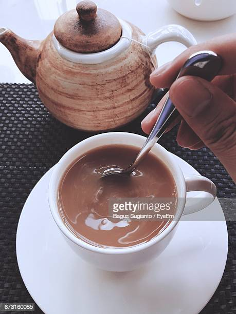 Cropped Hand Of Man Stirring Tea In Cup