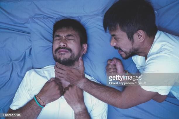 cropped hand of man suffocating twin brother sleeping on bed - killing stock pictures, royalty-free photos & images