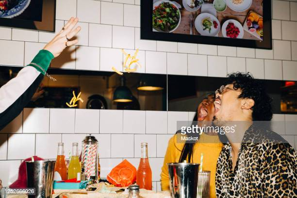 cropped hand of man throwing french fries at male and female friends with open mouth in cafe - bizarre stock pictures, royalty-free photos & images
