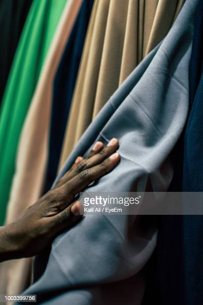 cropped hand of man touching fabric at shop - nigeria stock pictures, royalty-free photos & images