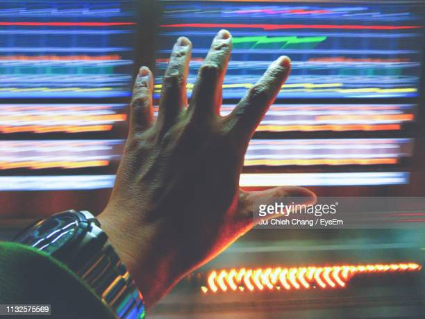 Cropped Hand Of Man Touching Illuminated Device Screen