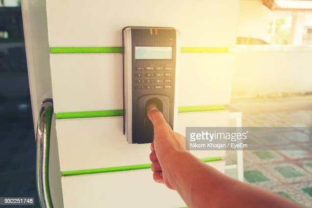 Cropped Hand Of Man Using Biometric Fingerprint Scanner On Wall