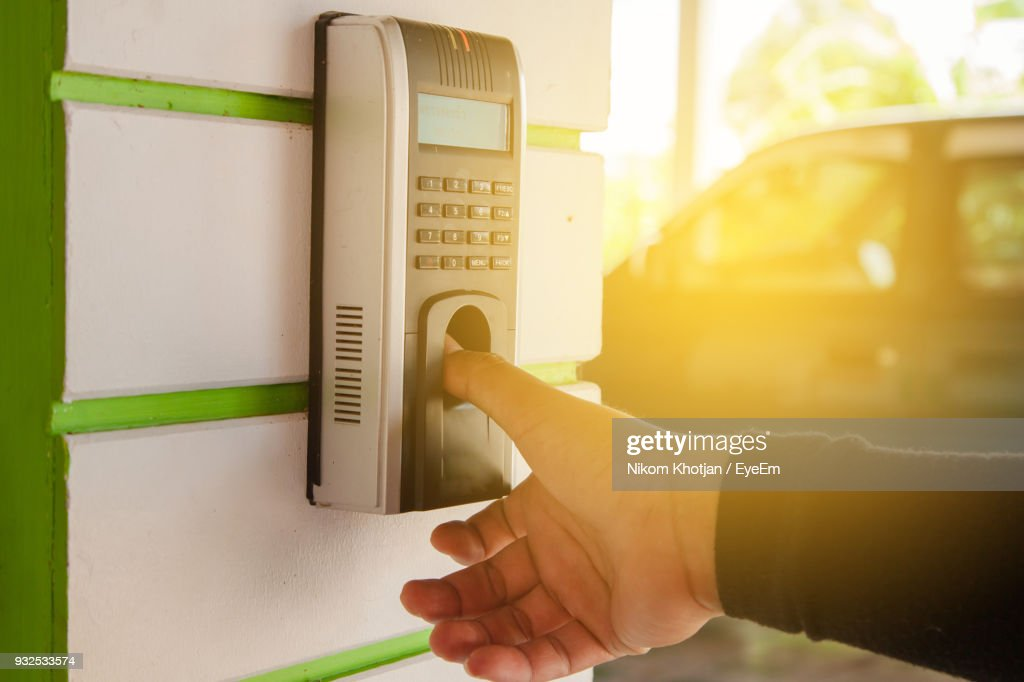 Cropped Hand Of Man Using Biometric Fingerprint Scanner On Wall : Stock Photo