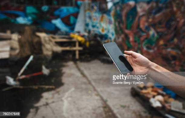 Cropped Hand Of Man Using Mobile Phone While Standing On Street