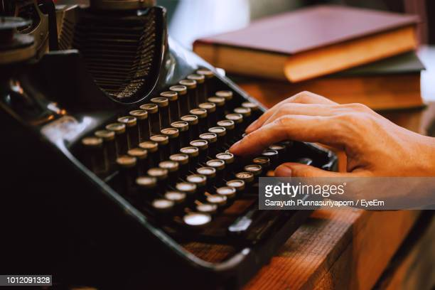 cropped hand of man using typewriter - authors photos et images de collection