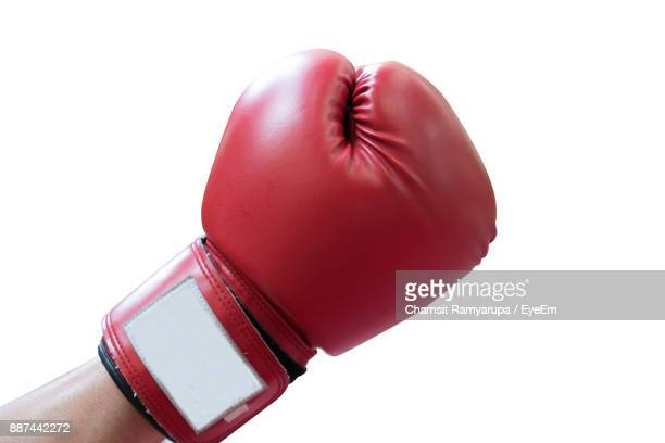 cropped hand of man wearing boxing glove over white background - boxing gloves stock photos and pictures