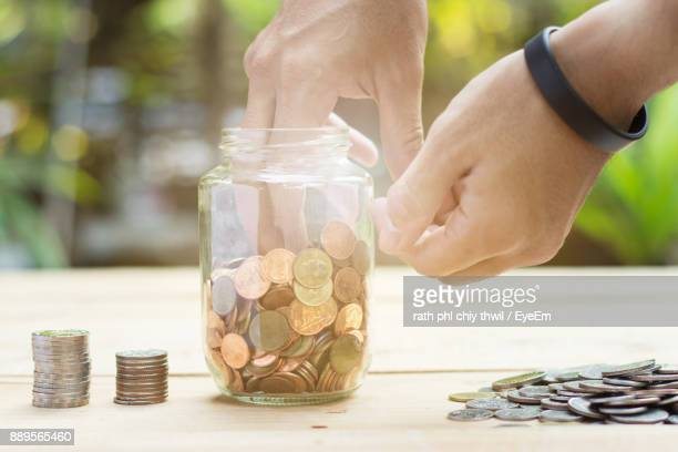 Cropped Hand Of Man With Coins In Jar On Wooden Table