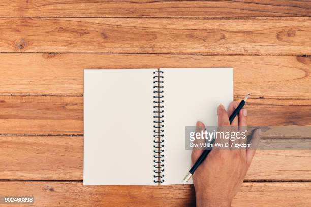 Cropped Hand Of Man With Pencil And Blank Book On Wooden Table