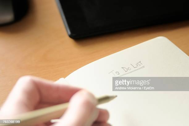 cropped hand of man writing in notepad at desk in office - list stock pictures, royalty-free photos & images
